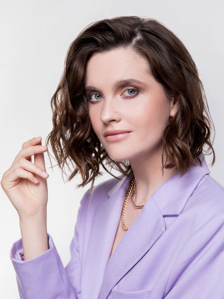 Dark-haired woman with lilac blazer looks at the camera.