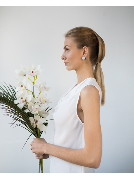 Woman with edgy hairstyle in a wedding dress, holding flowers and leaves