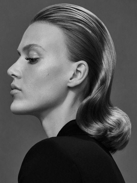 Schwarz-Weiß-Foto einer Frau mit zurückgekämmtem, welligem Haar