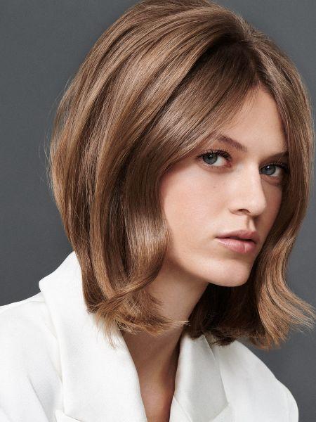 Frau mit brünettem Haar im 60s-Look und weißem Oberteil, die in die Kamera schaut
