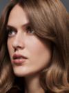 Nahaufnahme einer Frau mit brünettem, welligem Haar