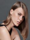Seitenansicht einer Frau mit halblangem, brünettem Haar, die in die Kamera schaut