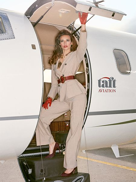 Perfectly-styled businesswoman poses on plane steps before boarding