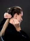 Junge Frau stylt sich eingedrehte Dutch Braids