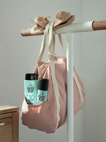 Nutri-Balance Repair Produkte stecken in einer rosafarbenen Ballett-Sporttasche, die an einem Barren hängt