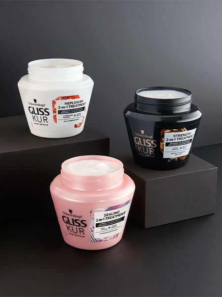 Three Gliss Kur 2-in-1 hair masks displayed on black boxes