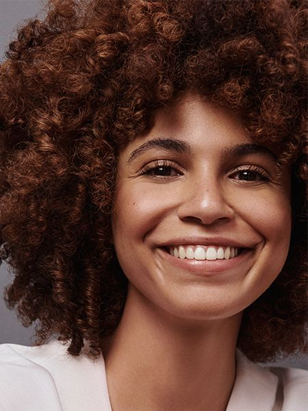 Woman with brunette curly afro wearing white top and smiling