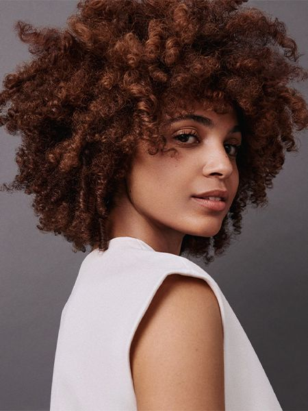 Woman with brunette curly afro looking over her right shoulder