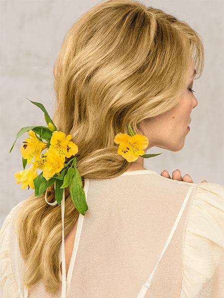 Blonde Frau mit langen Blonden Haaren hat Blumen im Haar