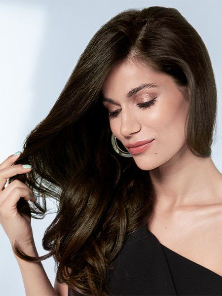 Dark-haired woman touches her long, full hair.