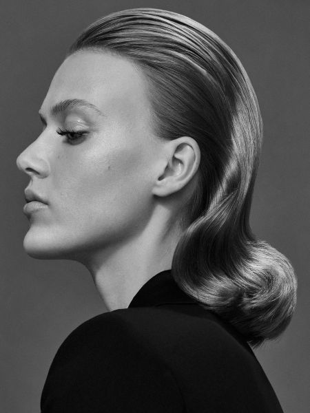 Black and white photo of woman with wavy slicked back hair.