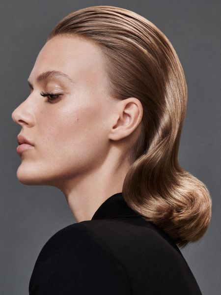 Brunette woman with slicked back hair with a wave in it.
