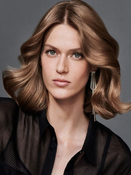 Brunette woman with wavy hair, curled back from the front.