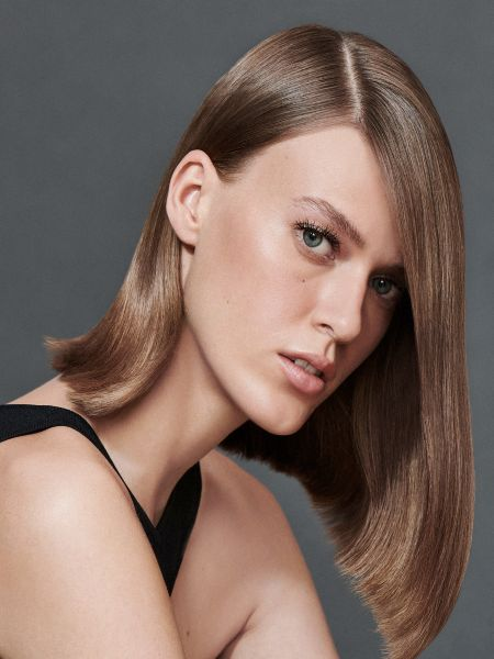 Brunette woman with straight hair in a side part, wearing a black tank top.