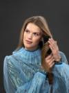 Model mit langen hellbraunen Haaren stylt sich