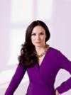 Dunkelhaarige Frau mit klassischen Wellen in einem violetten Kleid