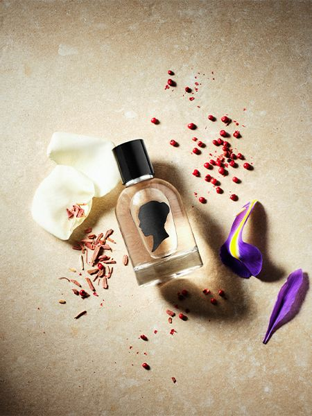 Bottle of Martha hair fragrance lies on the floor, surrounded by flower petals and other ingredients
