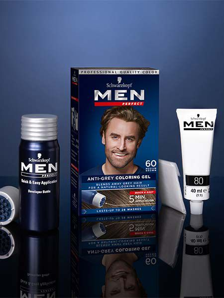 A box of Men Perfect Anti-Grey Coloring Gel stands on a glossy dark blue surface with a blue background surrounded by its contents