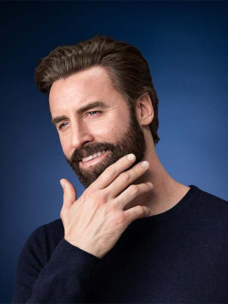 Man looking into the distance smiling and touching his dark brown colored beard