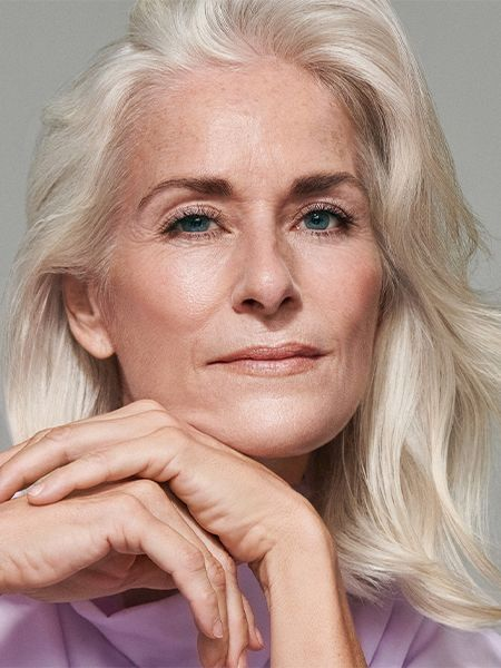 Mature woman with light blonde hair rests her chin on her hands