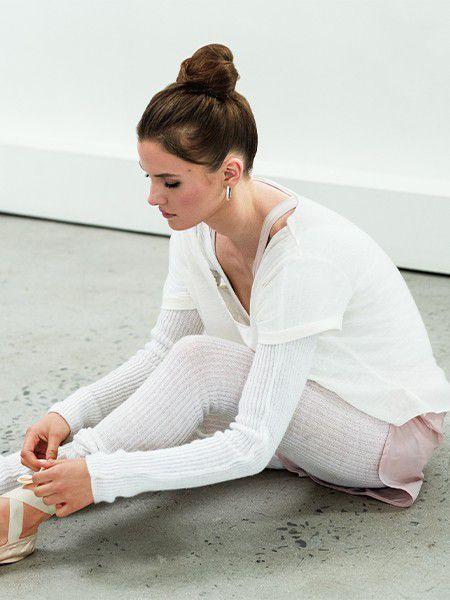 Balerina smjeđe kose s visokom punđom sjedi na podu i veže papučice.