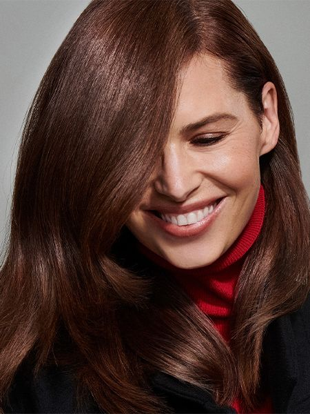 Woman with sleek brunette hair, black winter coat, and red turtleneck sweater