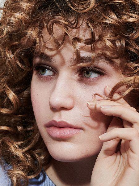 Woman with dark blonde, curly hair twirls a strand of hair around her finger