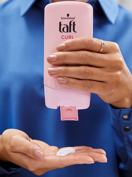 Woman squirts Taft Curl Balm onto her hand
