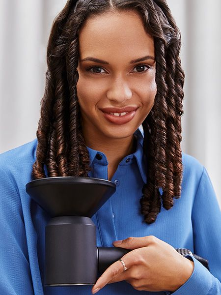 Woman with tight curls uses a diffuser to dry hair