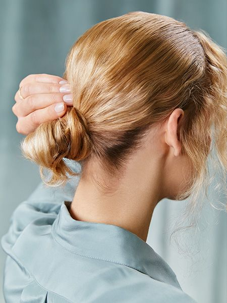 Woman holds her low bun in place with one hand