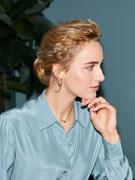 Woman rests her chin on her hand and looks to the side to show off her low bun hairstyle