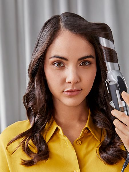Woman using a curling iron to create waves