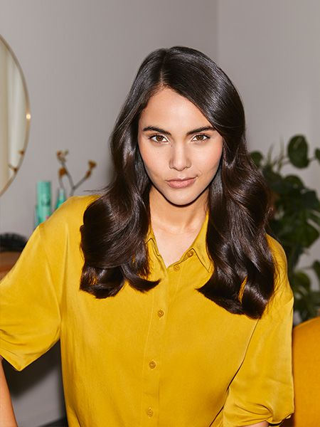 Woman looks confidently into the camera and has shiny soft waves