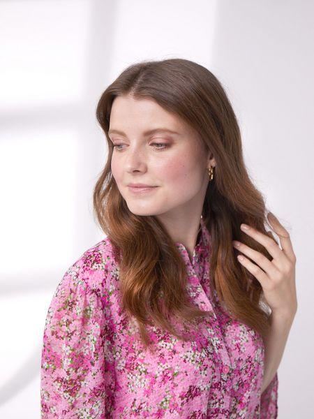Braunhaarige Frau in pinkfarbener Blümchenbluse streicht sich die Haare aus dem Gesicht