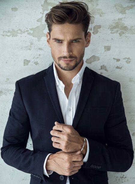 Homme blond avec une chemise blanche et un costume bleu en train de toucher son bracelet en argent