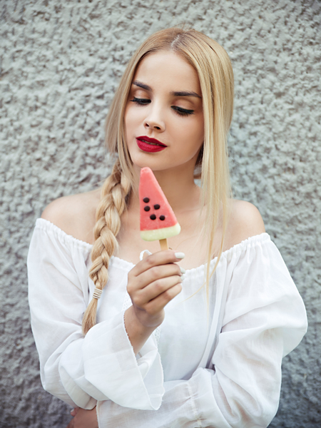 Young woman with blonde hair holding a popsicle