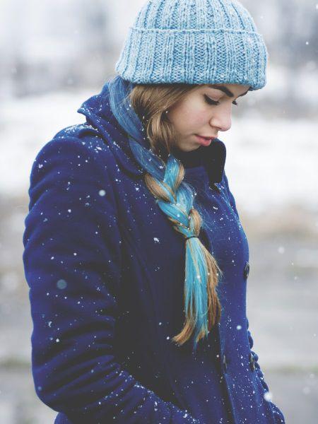 Giovane donna sotto la neve in abbigliamento invernale, con treccia laterale bionda e azzurra.