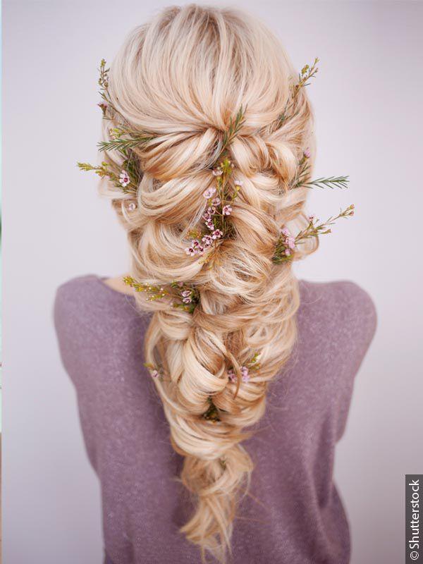 Donna di spalle con capelli biondi e treccia voluminosa con fiori