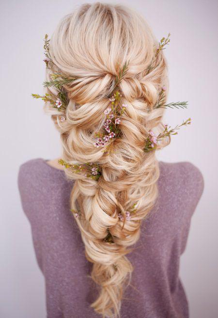 Donna di spalle con acconciatura intrecciata molto morbida e voluminosa, impreziosita da accessori floreali