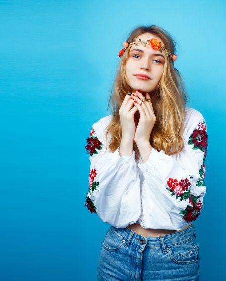 Giovane donna con capelli lunghi sciolti e corona di fiori a metà fronte