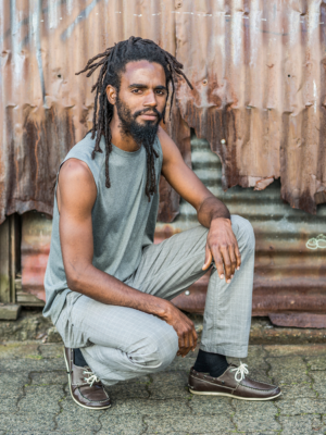 Model with black hair and dreadlocks, crouching down.