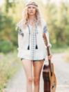 Hippie girl walking down a path holding a guitar