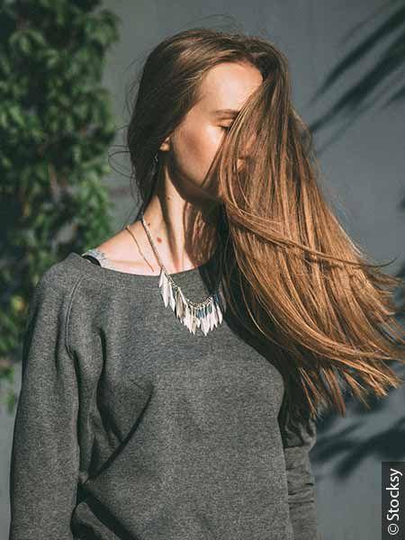 Donna con capelli lunghi al vento, di color castano chiaro.