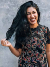 Schwarzhaarige Frau in gemustertem Shirt trägt eine lange Lockenfrisur