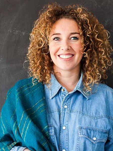 Blonde Frau mit kleinen Locken trägt ein blaues Jeanshemd