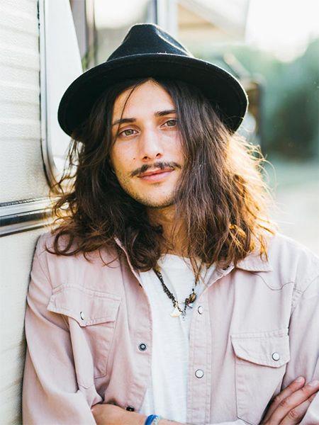 Mann mit langen braunen Haaren, Schnurrbart und schwarzem Hut lächelt in die Kamera