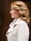 Blonde Frau mit großen Locken trägt einen cremefarbenen Mantel