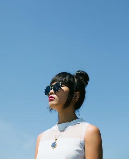 Donna con capelli neri, occhiali scuri, chignon e frangia perfettamente dritta e lucida