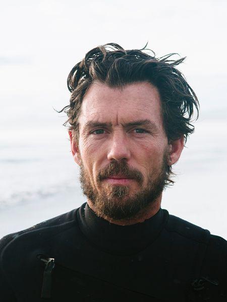 Braunhaariger Mann mit Surferfrisur im Wet-Look