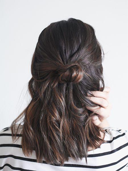 Dunkelhaarige Frau trägt ihre Haare nach hinten gebunden